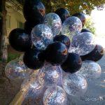 связка черных и прозрачных шаров с серебрянными квадратными конфетти