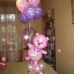 розовый медвежонок на полянке держит в лапке гелевые шарики
