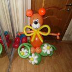 фигура из воздушных шариков медвежонок на полянке с цветами и подком